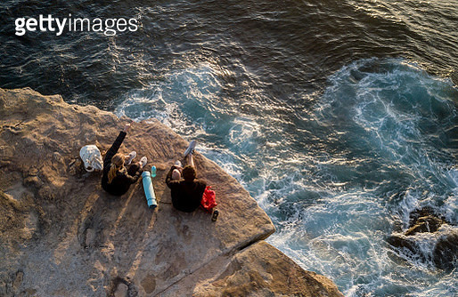 Hikers sitting on the edge of a cliff taking a break from the walk - gettyimageskorea