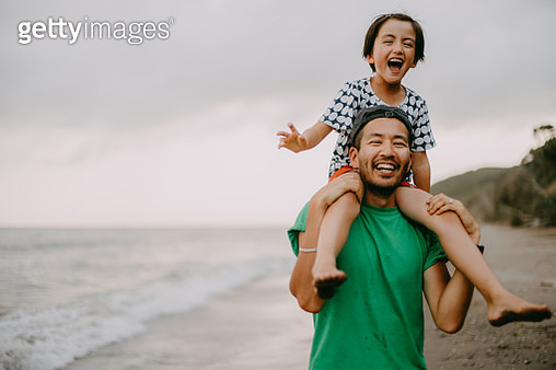 Cheerful father carrying his daughter on shoulders on beach - gettyimageskorea
