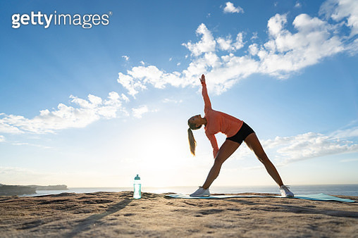 Woman meditating outdoors by the sea - gettyimageskorea
