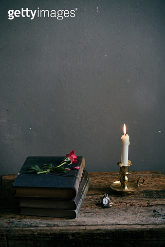 Rose on a stack of books, candle and watch on a wooden table - gettyimageskorea