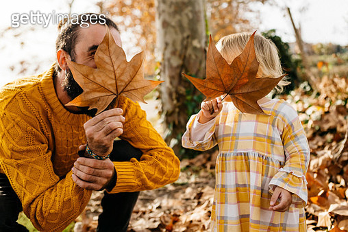 Father and daughter enjoying a morning day in the park in autumn, playing with autumn leaves - gettyimageskorea