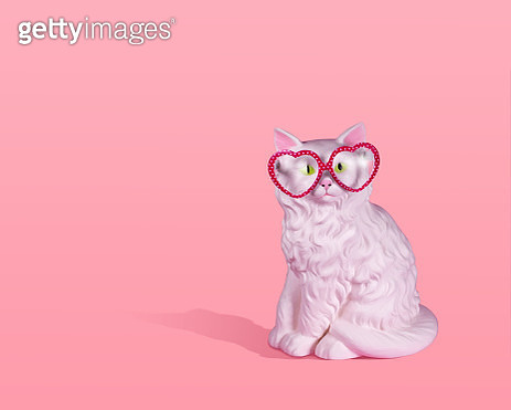 Large white vintage ceramic cat wearing pink and white polka dot glasses on a pink background with strong shadow and room for copy. - gettyimageskorea