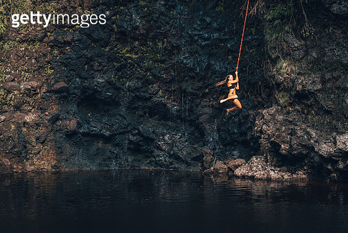 Young woman swings on rope, above natural pool - gettyimageskorea