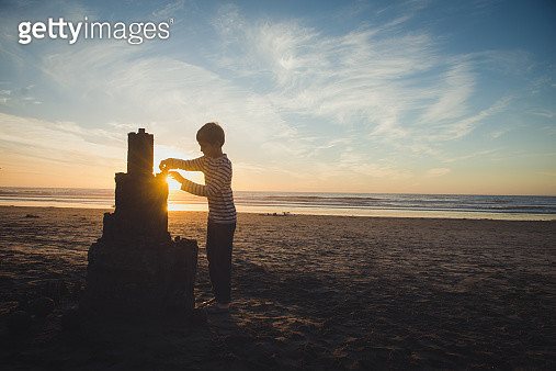 Boy with very large sandcastle at sunset on beach - gettyimageskorea