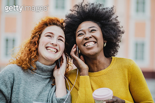 Photo of two female friends on the street holding smartphone and listen to the music together - gettyimageskorea
