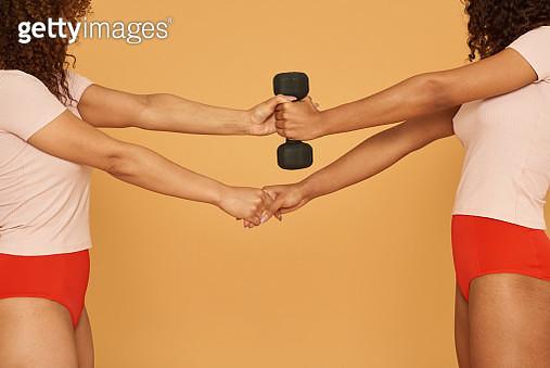 Women using teamwork to lift weight - gettyimageskorea