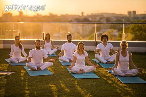Large group of athletic people practicing Yoga on a penthouse balcony. - gettyimageskorea