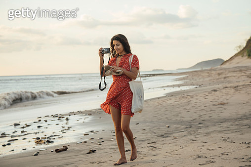 Young woman on beach holding camera - gettyimageskorea