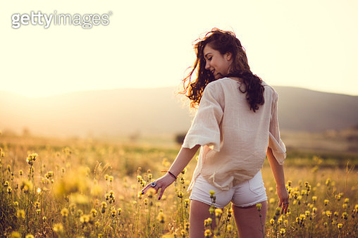 Attractive Young Woman In Yellow Sunny Field - gettyimageskorea