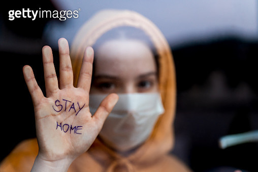 Teenage girl with a surgical maks standing and looking through the window and showing 'stay home' message written on her hand - gettyimageskorea