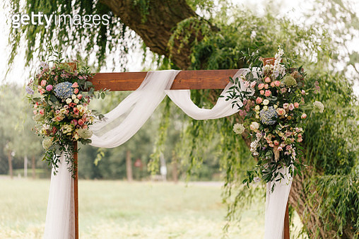 Wedding arch decorated with flowers and greenery in rural area - gettyimageskorea