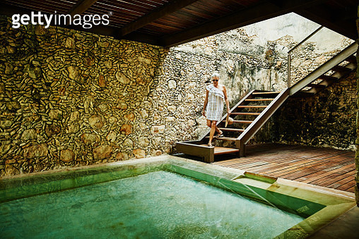 Senior woman descending stairs to spa at luxury resort - gettyimageskorea