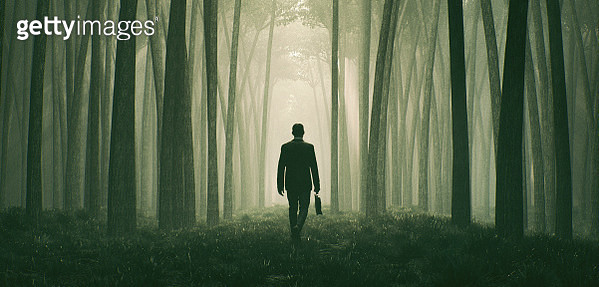 Lost businessman walking in the forest at night - gettyimageskorea