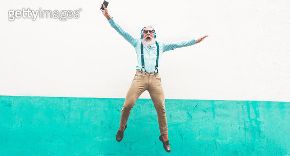 Man Listening Music While Jumping Against Wall - gettyimageskorea
