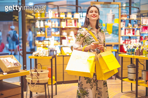 Young woman is buying presents at the shopping mall - gettyimageskorea