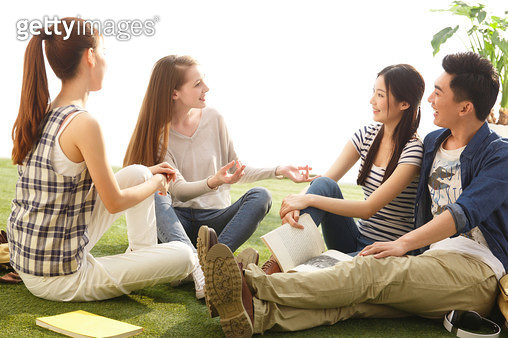 Young college students sit on the grass to chat - gettyimageskorea
