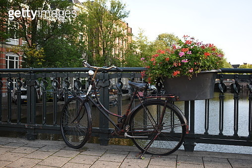 Bicycle parked by the railings of Amsterdam's canals. - gettyimageskorea