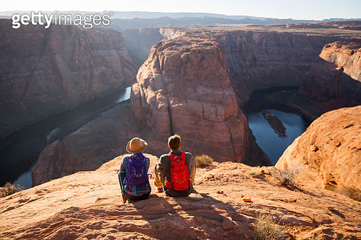 A couple sitting at an overlook at Horseshoe Bend, Arizona. - gettyimageskorea