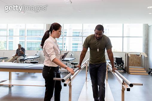 Female physical therapist watches injured veteran walk - gettyimageskorea
