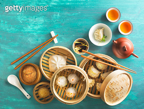 Assorted Chinese food dim sum, steamed bun, dumpling and traditional tea set on green textured table top. Flat lay overhead view text space image. - gettyimageskorea