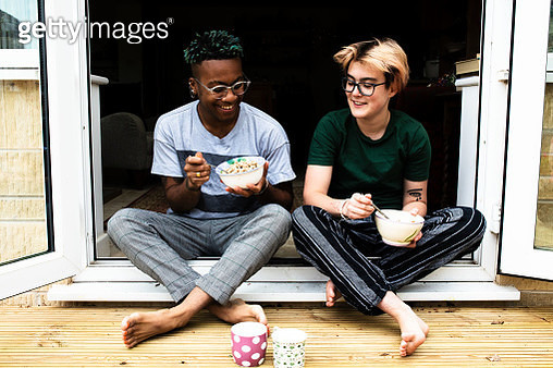 A young LGBT couple sat in a doorway eating breakfast together - gettyimageskorea