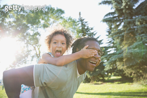 Portrait of playful girl covering fathers eyes in park - gettyimageskorea