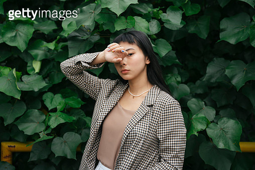 Portrait Of Young Woman Standing Against Plants - gettyimageskorea