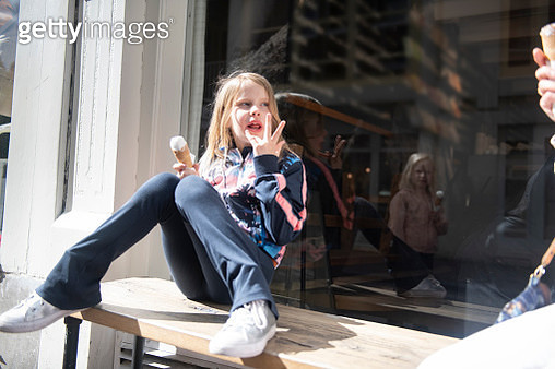 Girl sitting on a bench, licking her fingers. Her sister reflected in the shop window. - gettyimageskorea
