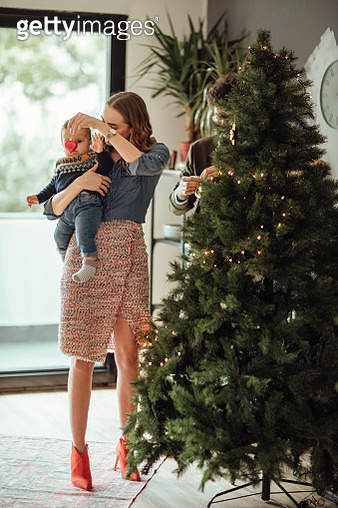 Happy family decorating Christmas tree - gettyimageskorea