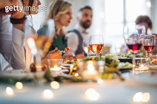 A Big Family Sitting At A Table On A Indoor Birthday Party, Eating - gettyimageskorea