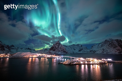 Aurora borealis. Lofoten islands, Norway. Aurora. Green northern lights. Starry sky with polar lights. Night winter landscape with aurora, sea with sky reflection and snowy mountains. - gettyimageskorea