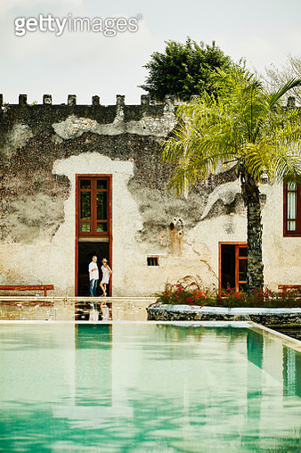 Senior couple in discussion while standing in doorway of tropical luxury resort - gettyimageskorea