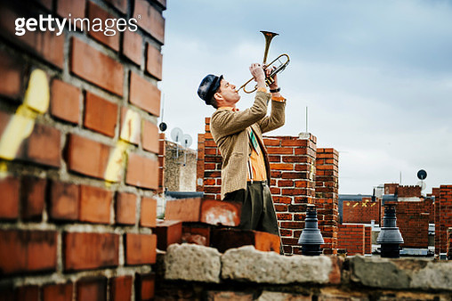 A trumpet player playing on a rooftop - gettyimageskorea