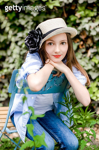 Portrait of girl wearing summer hat sitting on chair in the garden - gettyimageskorea