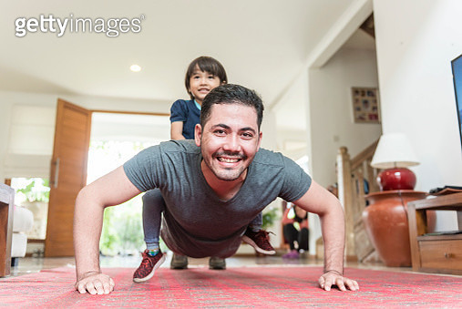 Father and son doing push up on a living room - gettyimageskorea