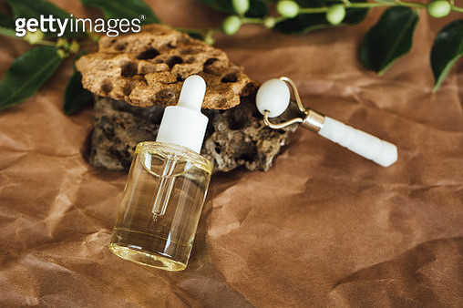 Essential oil in a transparent glass bottle and white jade roller near stones and plants. Trendy selfcare products of the year - gettyimageskorea