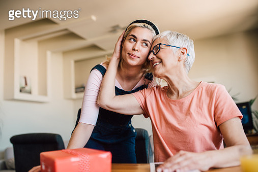 Woman being hugged by her mother after giving her a present - gettyimageskorea