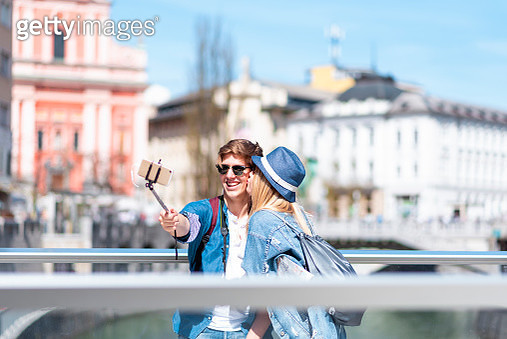 Two cheerful young tourists in town taking selfie on a sunny day - gettyimageskorea