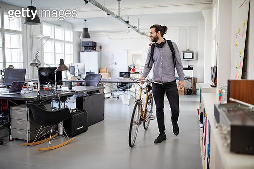 Businessman with a bicycle in office - gettyimageskorea