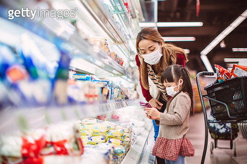Mom & daughter with surgical masks doing grocery shopping for diary products in supermarket - gettyimageskorea