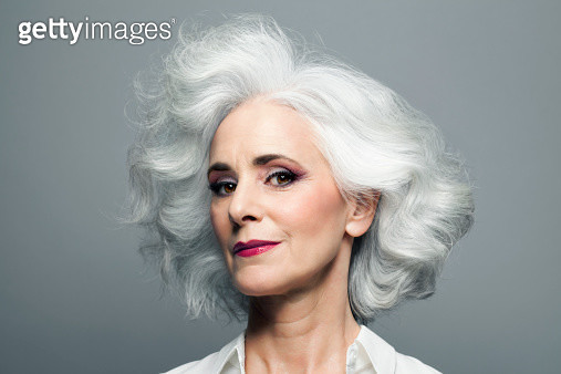 Mature woman with medium length, big, wavy, silvery, grey hair in front of grey background wearing make up red lip stick, portrait. - gettyimageskorea