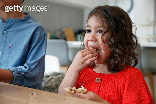 Cute girl in red top eating homemade cake, messy hands, hungry, indulgence - gettyimageskorea