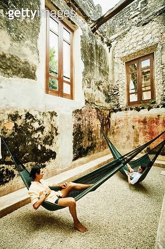 Two male friends relaxing in hammocks at luxury resort - gettyimageskorea