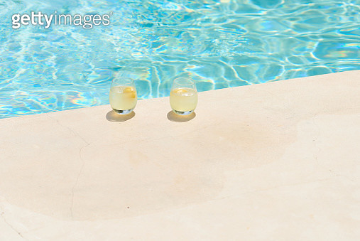 Two refreshing drinks sat poolside - gettyimageskorea