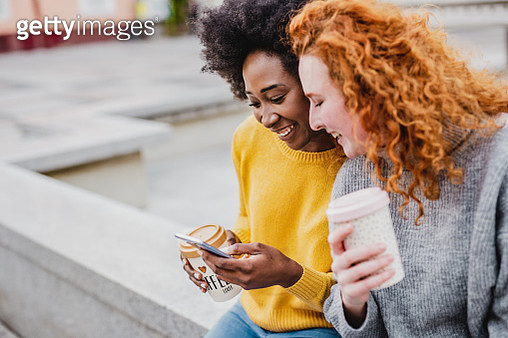 Photo of two female friends sitting on the street holding smartphone and reusable coffee cups - gettyimageskorea
