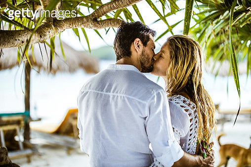 Young couple in love kissing with their eyes closed during summer day on the beach. - gettyimageskorea