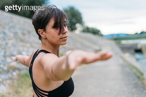 Young adult woman practicing yoga near a river - gettyimageskorea