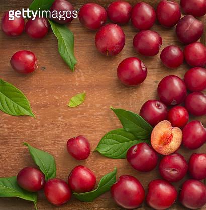 Fresh plum on wooden background. Overhead view. - gettyimageskorea