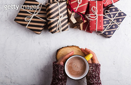 Overhead view of woman holding mug of hot cocoa and Christmas gift boxes - gettyimageskorea