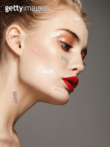 Beautiful woman with baby text applique on her face - gettyimageskorea